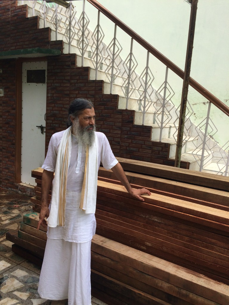 Babaji resting after examining a stack of wood purchased for building beds and doors