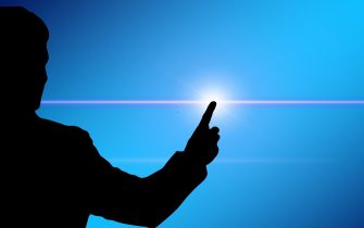 silhouette of man with raised finger and light beam